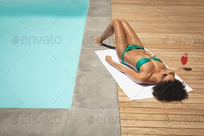 High view of young African American woman relaxing at poolside in her backyard on a sunny day