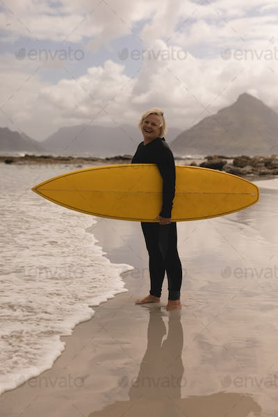 Side view of an active senior woman standing with surfboard on the beach
