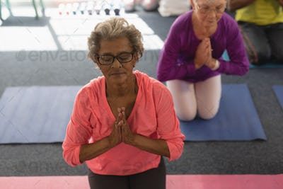 Front view of senior woman doing yoga in fitness studio