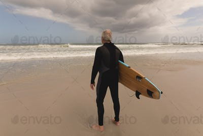 Rear view of senior man standing with surfboard on the beach