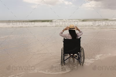 Rear view of disabled young woman holding hat and sitting on wheelchair at beach