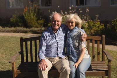 Portrait of active senior Caucasian couple sitting with arm around in the park