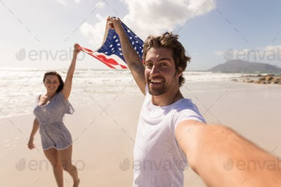 Front view of a happy young couple holding american flag and having fun on beach in the sunshine