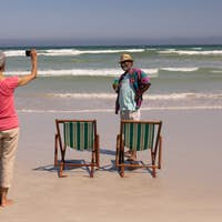Rear view of senior woman clicking photo of senior man on beach in the sunshine