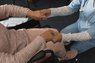 Low section of female doctor holding hands of disable senior woman at home