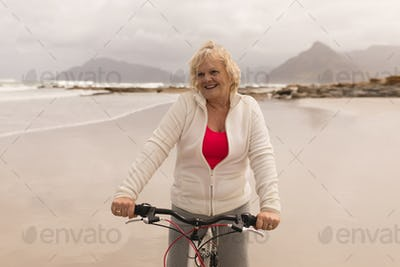 Front view of active senior woman riding a bicycle on the beach against mountains in the background