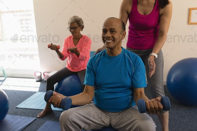 Young female trainer assisting senior man making exercices on exercice ball in fitness studio