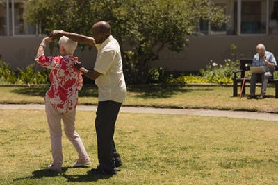 Side view of senior couple dancing together in garden on as sunny day