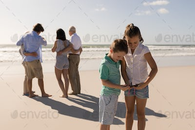 Siblings using mobile phone while their family standing in background on beach