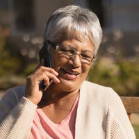 Close-up of active mixed-race senior woman talking on mobile phone in park on sunny day