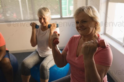 Front view of active senior women exercising with dumbbells at home