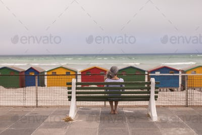 Rear view of senior woman sitting on promenade bench at beach in the sunshine