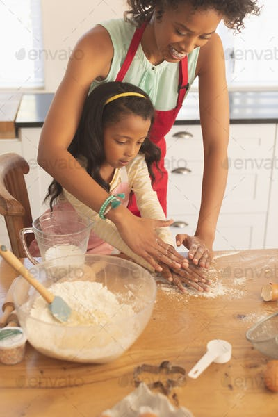 High angle view of happy African American mother and daughter kneading dough in kitchen at home