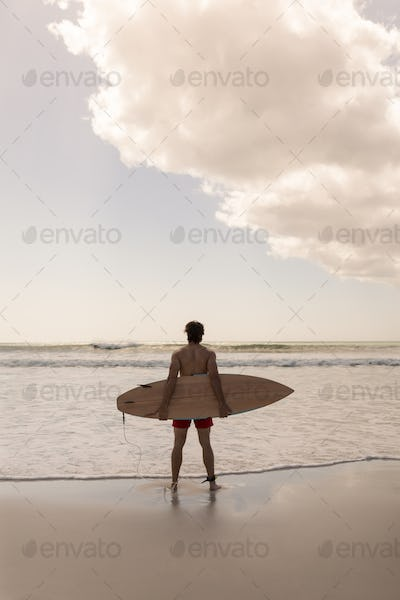 Rear view of shirtless young male surfer with surfboard standing on beach