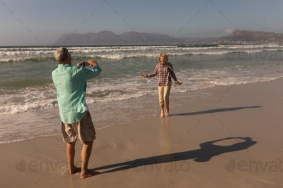 Rear view of active senior man clicking photo of senior woman on the beach