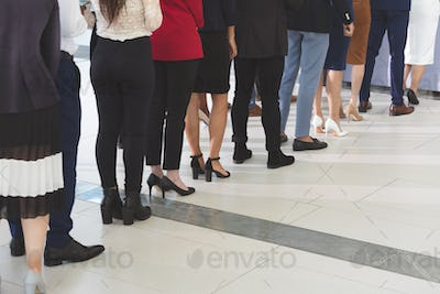 Low section of diverse business people checking in at conference registration table in office lobby