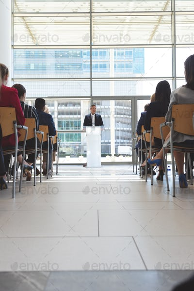 Low angle view of male mixed race speaker speaks in a business seminar in modern office building