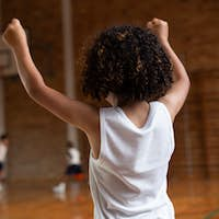 Schoolboy cheering with arms up and supporting his team in the basketball court at school