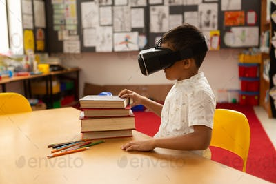 Side view of mixed-race schoolboy using virtual reality headset at desk in a classroom