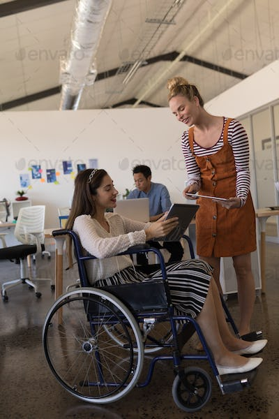 Pretty disabled female executive discussing with coworker over digital tablet in modern office