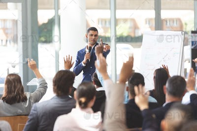 Young businessman speaking at business seminar with diverse group of people raising their hand