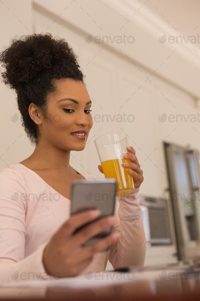 Side view of beautiful African American woman having orange juice while using mobile phone at home