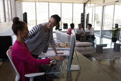 Beautiful female executives interacting with each other at desk in modern office