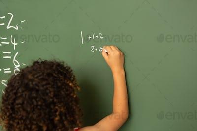 schoolgirl solving mathematics calculations on green board in classroom at school