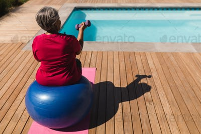 Senior woman exercising with dumbbells on a swiss ball in front of the swimming pool