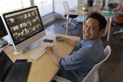Portrait of Asian male executive working on personal computer at desk in office