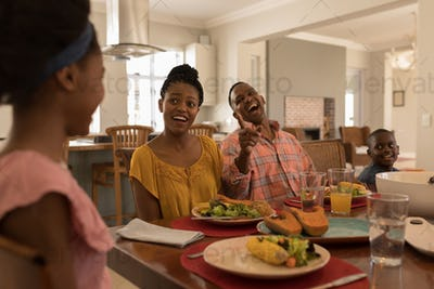 Front view of a happy African American family having meal together on dining table at home