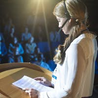 Side view of young Caucasian businesswoman in headset giving presentation in the auditorium