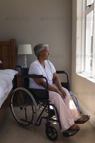 Front view of a thoughtful disabled senior African American woman looking through window at home