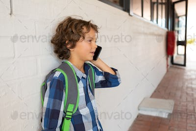 Schoolboy talking on mobile phone while leaning against a wall in the corridor at school