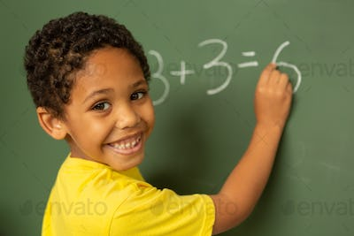 Happy schoolboy looking at camera while doing math on greenboard in a classroom at elementary school