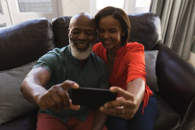Senior couple taking a selfie with mobile phone while sitting on a sofa in the living room