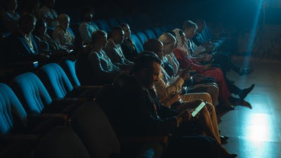 Side view of mixed race audience sitting in the auditorium and holding smartphone in their hands