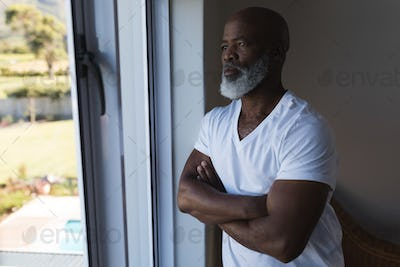 Thoughtful senior African American man looking through window with crossed arms at home
