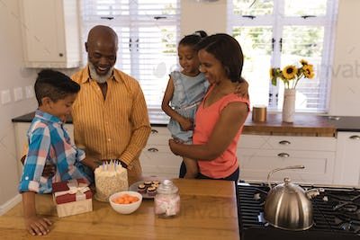 Multi-generation family celebrating birthday with delicious sweets at home