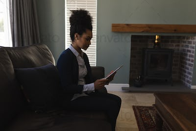 Female real estate agent a using digital tablet while sitting on the sofa in living room at home