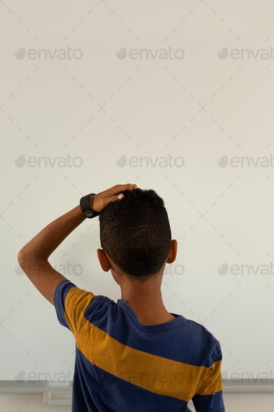 Rear view of mixed-race boy with hand on head standing against white background