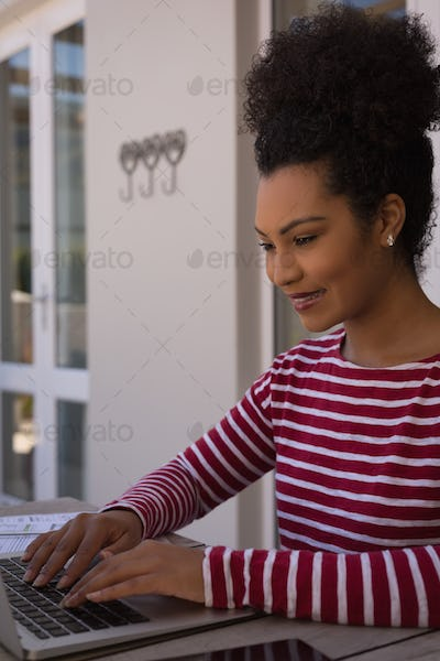 Side view of a beautiful African American woman using her laptop at home