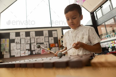 Front view of cute mixed-race schoolboy playing xylophone in a classroom at elementary school