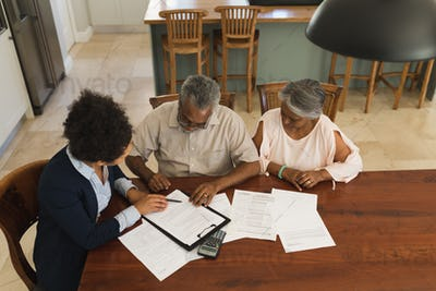 Female real estate agent and a senior couple discussing over documents at the table
