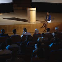 Businesswoman sitting at the side of the stage and having laptop in her hand in front of audience