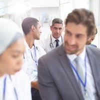 Front view of  diverse male doctors interacting with each other during seminar in conference room.
