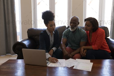 Female real estate agent and a senior couple discussing over documents while sitting on the sofa