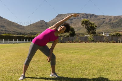 Beautiful young mixed-race woman performing stretching exercise in the backyard of home