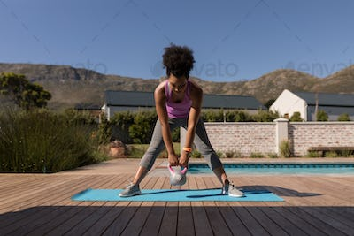 Woman exercising with kettlebell in front of the swimming pool in the backyard