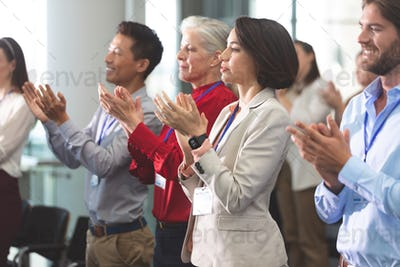 Side view of diverse business people applauding standing in a business seminar in office building